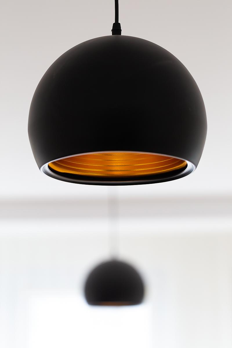 Czarna wisząca lampa z pomarańczowym wnętrzem