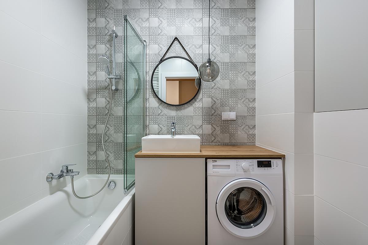 Biała łazienka szare kafelki okrągłe lustro
